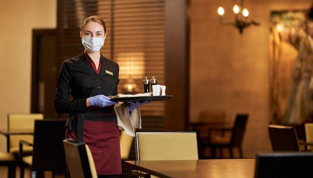 Pani w masce stoliki w eleganckiej restauracji