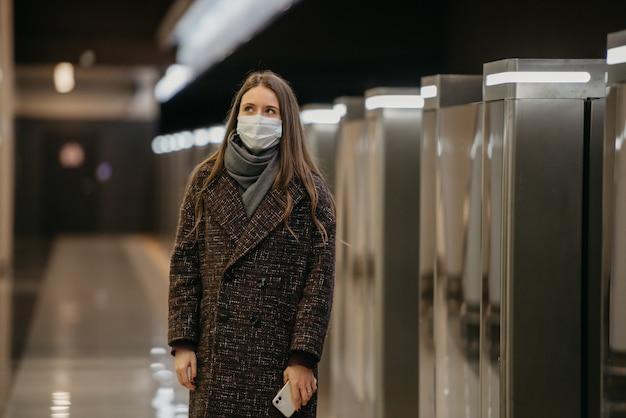 Pani w medycznej masce na twarz, aby uniknąć rozprzestrzeniania się koronawirusa, czeka na pociąg i trzyma telefon komórkowy na peronie metra. dziewczyna w masce chirurgicznej trzyma dystans społeczny w metrze
