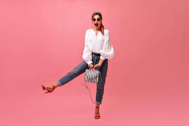 Pani w okrągłych okularach pozuje z torebką na różowym tle. pozytywna młoda kobieta w czerwonych okularach przeciwsłonecznych i jasnych ustach raduje się z kamery.