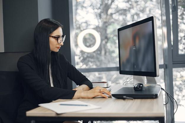 Pani w okularach. kierownik siedzi przy komputerze. kobieta pracuje w swoim biurze.