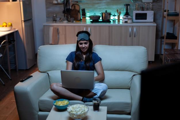 Pani w piżamie i osłonie oczu na czole pisząca na laptopie i oglądająca telewizję późno w nocy . freelancer pracuje siedząc na kanapie, czytając, pisząc, przeszukując przeglądanie na notebooku za pomocą technologii internetowej
