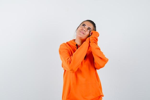 Pani w pomarańczowej bluzie opiera się na dłoniach jak poduszka i wygląda marzycielsko