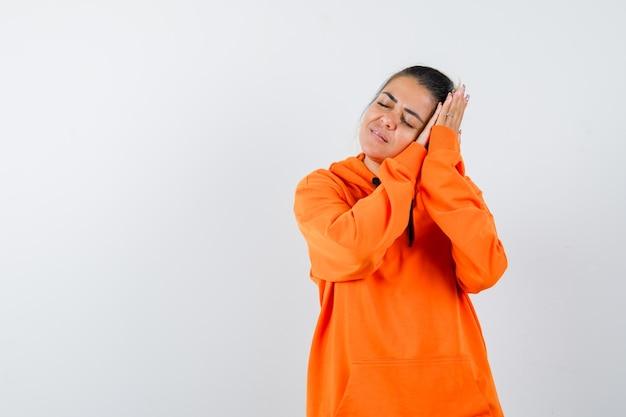 Pani w pomarańczowej bluzie opiera się na dłoniach jak poduszka i wygląda na spokojną