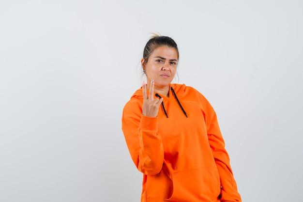 Pani w pomarańczowej bluzie z kapturem pokazująca dwa palce i wyglądająca na pewną siebie