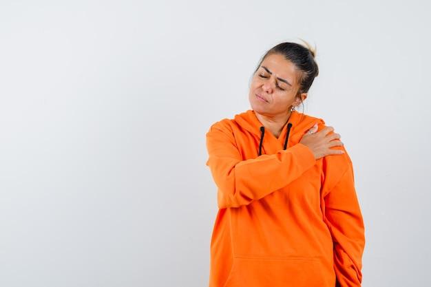 Pani w pomarańczowej bluzie z kapturem trzymająca rękę na ramieniu i wyglądająca spokojnie