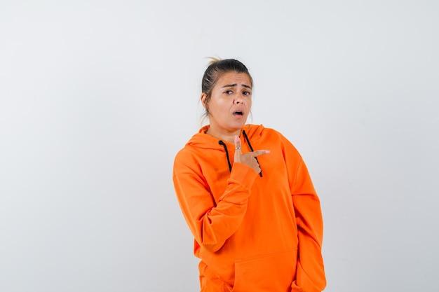 Pani w pomarańczowej bluzie z kapturem wskazująca na bok i wyglądająca na zdziwioną