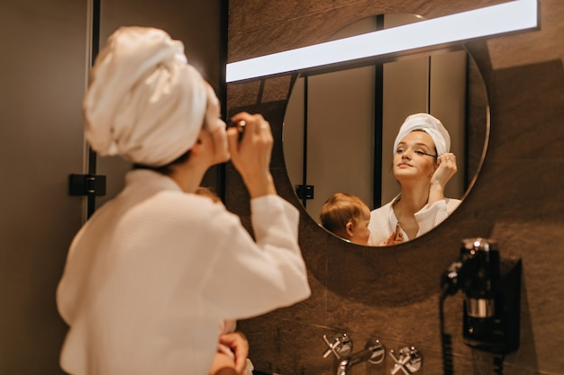 Pani w ręczniku na głowie robi makijaż oczu, patrząc w lustro w łazience i trzymając dziecko.