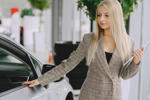 Pani w salonie samochodowym. kobieta kupuje samochód. elegancka kobieta w brązowym garniturze.