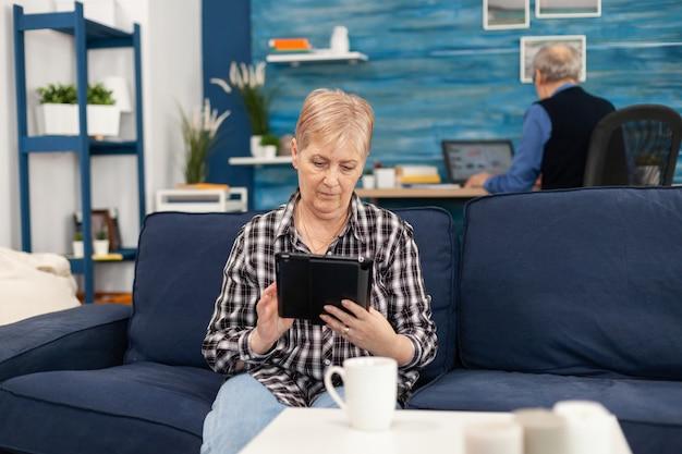 Pani w średnim wieku relaksuje się na kanapie, czytając na tablecie, ciesząc się treścią