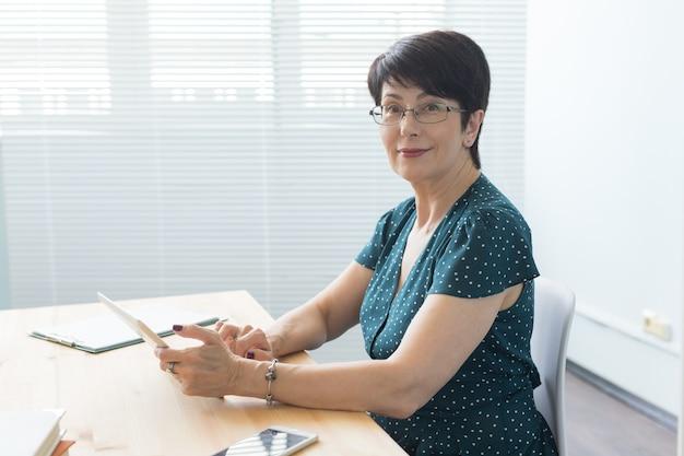 Pani w średnim wieku za pomocą tabletu w biurze