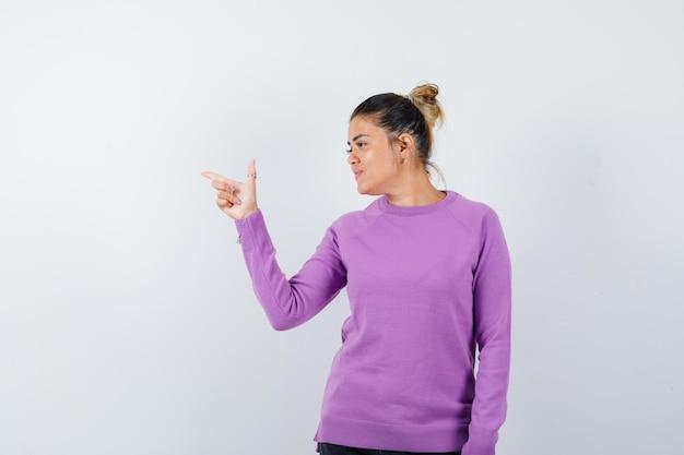 Pani w wełnianej bluzce skierowana w lewy górny róg i skupiona