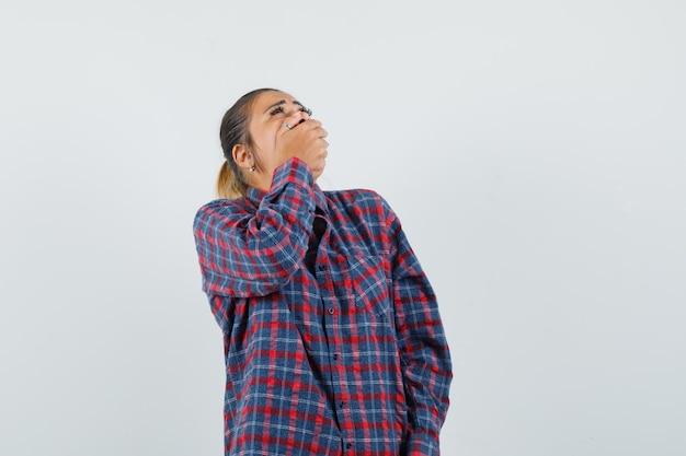 Pani w zwykłej koszuli, trzymając dłoń na ustach i wyglądająca żałośnie, widok z przodu.