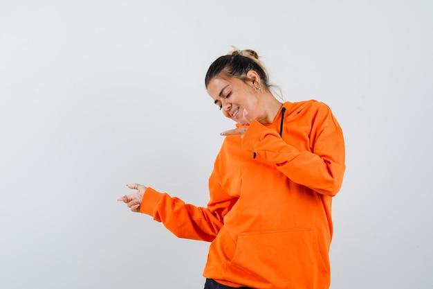 Pani wskazująca na bok w pomarańczowej bluzie z kapturem i patrząca wesoło