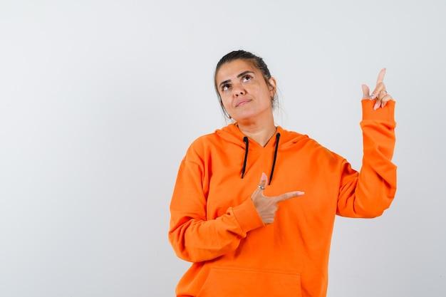 Pani wskazująca palcami w górę i na bok w pomarańczowej bluzie z kapturem i wyglądająca na marzycielską