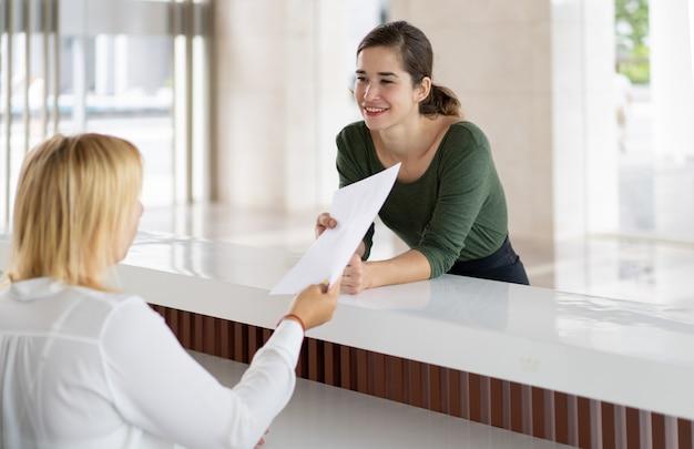 Pani z recepcji oferuje turystom możliwość wypełnienia dokumentów