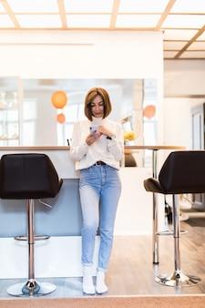 Pani z telefonem stoi w panoramicznej kuchni z jasnymi ścianami, wysokim stołem i krzesłami barowymi