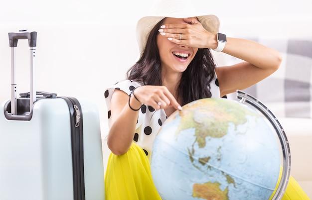 Pani z zawiązanymi oczami losowo wybiera miejsce na wakacje na świecie.