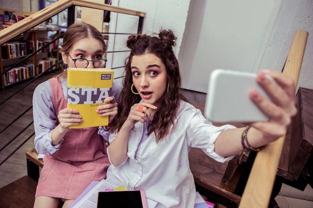 Panie same się fotografują. radosne, przystojne modne dziewczyny robią zdjęcie smartfonem i pokazują książkę edukacyjną