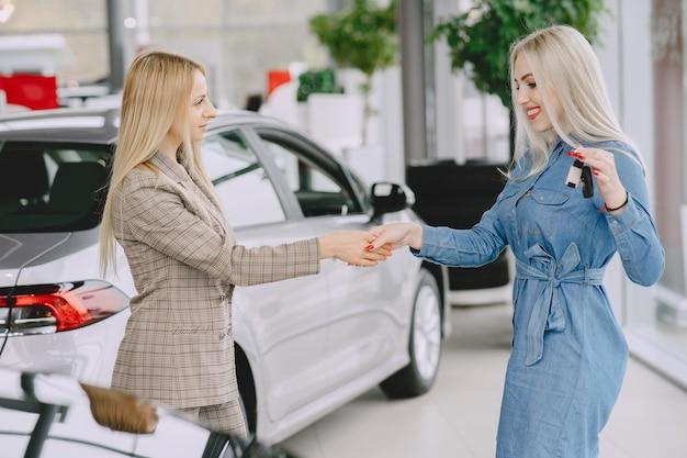 Panie w salonie samochodowym. kobieta kupuje samochód. elegancka kobieta w niebieskiej sukience. kierownik przekazuje klucze klientowi.