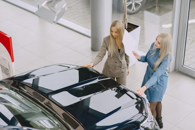Panie w salonie samochodowym. kobieta kupuje samochód. elegancka kobieta w niebieskiej sukience. menedżer pomaga klientowi.