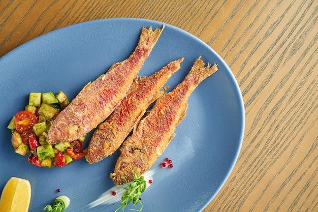 Panierowana smażona ryba morska (barwena) z przystawką z sałatką z awokado i pomidorami na niebieskim talerzu na drewnianej ścianie. z bliska, selektywne focus