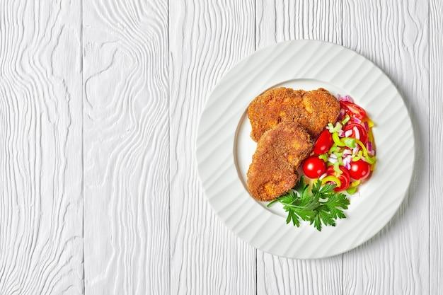 Panierowane kotleciki jagnięce podane z pomidorem, czerwoną cebulą, sałatką z zielonego pieprzu na białym talerzu na drewnianym stole, płasko leżąc, wolna przestrzeń