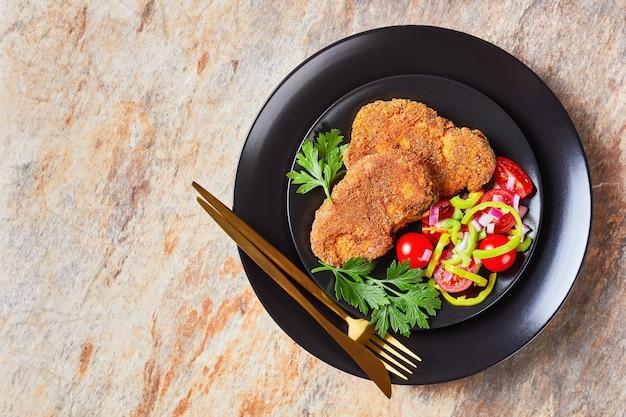 Panierowane kotleciki jagnięce zapiekane w piecu podawane z sałatką z pomidora, czerwonej cebuli i zielonego pieprzu na czarnym talerzu na kamiennym stole