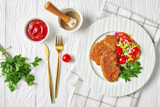 Panierowane kotlety jagnięce podane z pomidorem, czerwoną cebulą, sałatką z zielonego pieprzu na białym talerzu ze złotym widelcem i nożem na drewnianym stole, płasko leżące