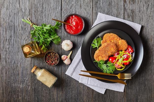 Panierowane kotlety jagnięce podane z pomidorem, czerwoną cebulą, sałatką z zielonego pieprzu na czarnym talerzu na drewnianym stole ze składnikami na powierzchni, widok krajobrazowy z góry, płasko leżący, wolna przestrzeń