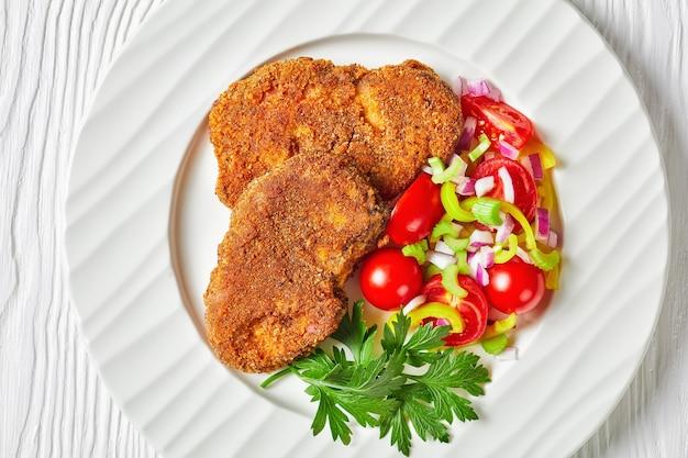 Panierowane kotlety jagnięce podawane z pomidorem, czerwoną cebulą, sałatką z zielonego pieprzu na białym talerzu na drewnianym stole, płasko świecki, zbliżenie, makro