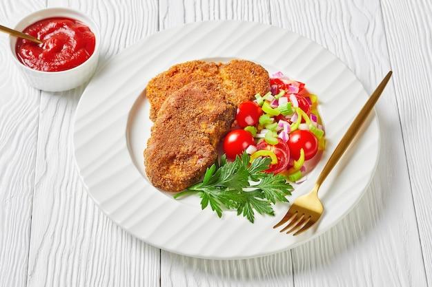 Panierowane kotlety jagnięce podawane z pomidorem, czerwoną cebulą, sałatką z zielonego pieprzu na białym talerzu na drewnianym stole, widok krajobrazu z góry, zbliżenie