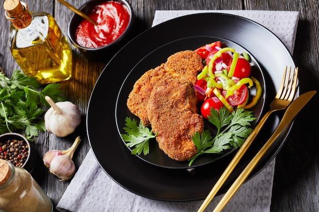 Panierowane kotlety jagnięce podawane z pomidorem, czerwoną cebulą, sałatką z zielonego pieprzu na czarnym talerzu na drewnianym stole, widok na krajobraz z góry