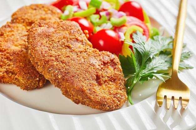 Panierowane kotlety jagnięce podawane z sałatką z pomidorów, czerwonej cebuli i zielonego pieprzu na białym talerzu na drewnianym stole, zbliżenie