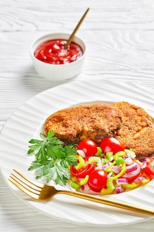 Panierowane kotlety jagnięce podawane z sałatką z pomidorów, czerwonej cebuli, zielonego pieprzu na białym talerzu na drewnianym stole, zbliżenie, widok pionowy z góry