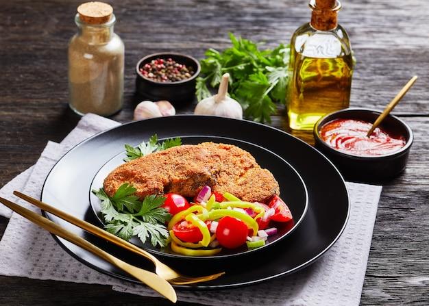 Panierowane kotlety jagnięce podawane z sałatką z pomidorów, czerwonej cebuli, zielonego pieprzu na czarnym talerzu na drewnianym stole ze składnikami na powierzchni, widok na krajobraz