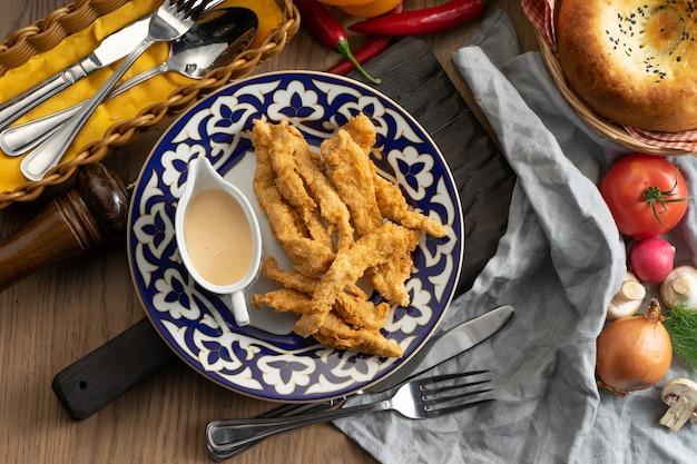 Panierowane nuggetsy z kurczaka z sosem serowym na talerzu z tradycyjnym uzbeckim
