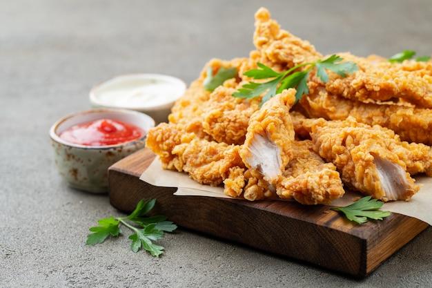 Panierowane paski kurczaka z dwoma rodzajami sosów.