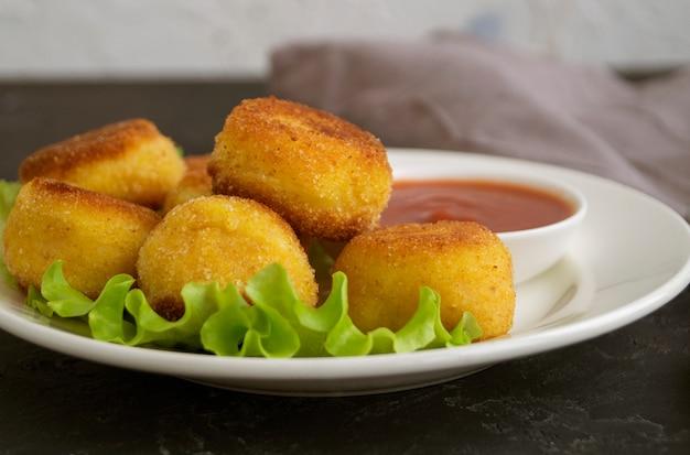 Panierowane smażone kulki ziemniaczane z sosem pomidorowym