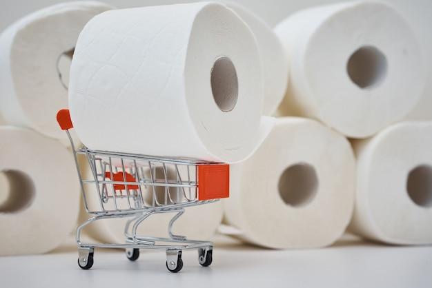 Panika zakupowa paniki na temat koncepcji koronawirusa covid-19. rolka papieru toaletowego w wózku na zakupy. ludzie gromadzą niezbędne produkty do domowej kwarantanny