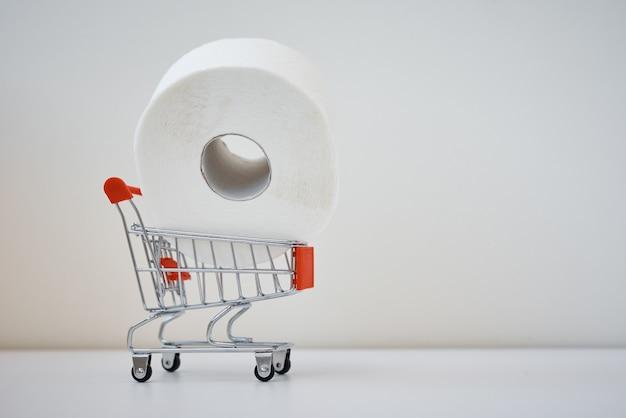 """Panika zakupowa paniki na temat koncepcji koronawirusa covid-19. rolka papieru toaletowego w wózku sklepowym z napisem """"panika stop""""."""