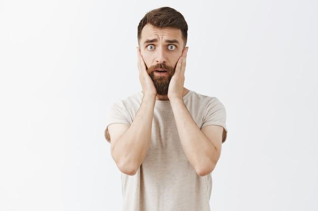 Panikując, przerażony brodaty mężczyzna pozuje przy białej ścianie