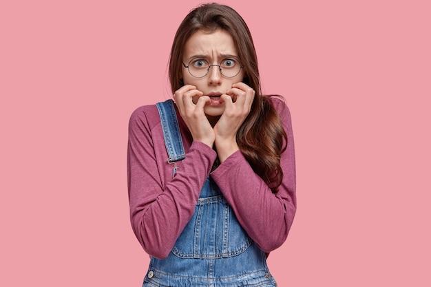Panikująca kobieta obgryza paznokcie dłoni, wygląda na zdenerwowaną i przestraszoną, nosi okrągłe okulary, dżinsowy kombinezon, odizolowana na różowej przestrzeni