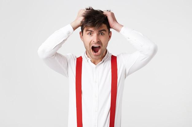 Panikujący mężczyzna chwycił dłonie za włosy na głowie, nosi koszulę i czerwony szelki,