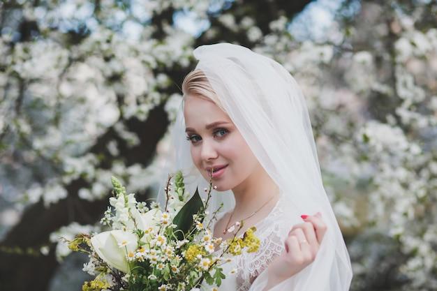 Panna młoda blondynka trzyma bukiet ślubny w parku wiosny, suknia ślubna