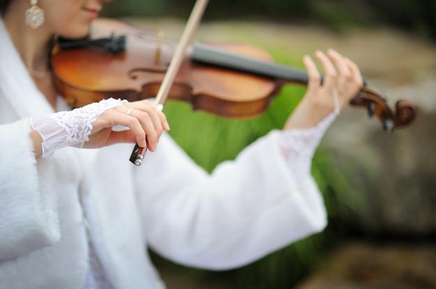 Panna młoda gra na skrzypcach dla pana młodego w parku latem.