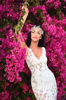 Panna młoda i ceremonia ślubna. kobieta w białej sukni ślubnej w ogrodzie. ślubna moda i uroda. elegancja i moda model dziewczyna w różowy kwiat.