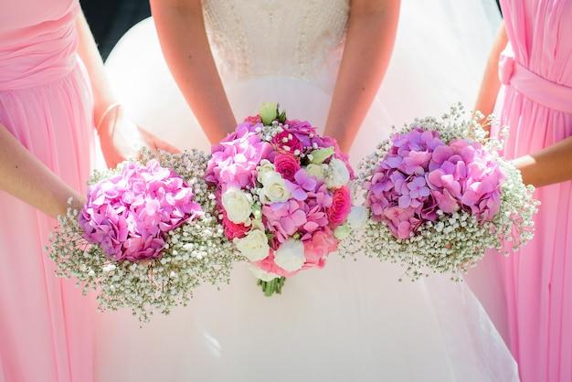 Panna młoda i druhna trzymają ręce razem z bukietami ślubnymi