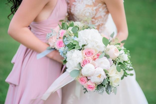 Panna młoda i druhna w różowej sukience przytulają się do siebie, stojąc przy bukietach ślubnych