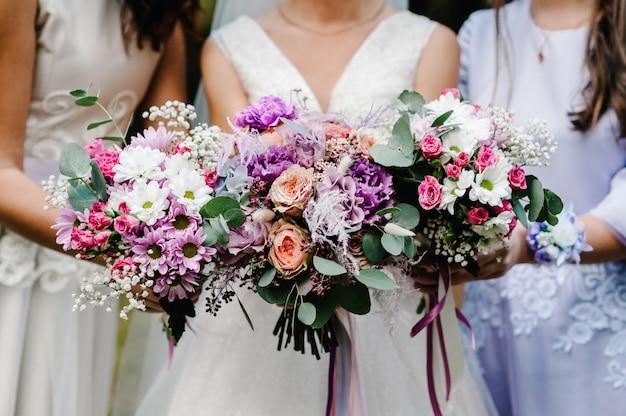 Panna młoda i druhny w eleganckiej sukience stoją i trzymają za rękę bukiety pastelowych różowych kwiatów i zieleni ze wstążką.