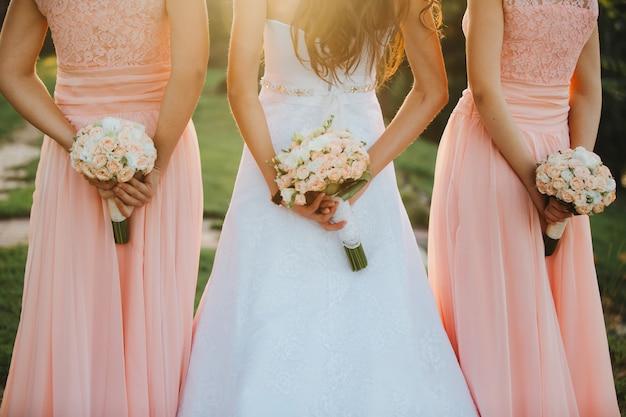 Panna młoda i druhny w eleganckiej sukni stoją i trzymają bukiet dłoni